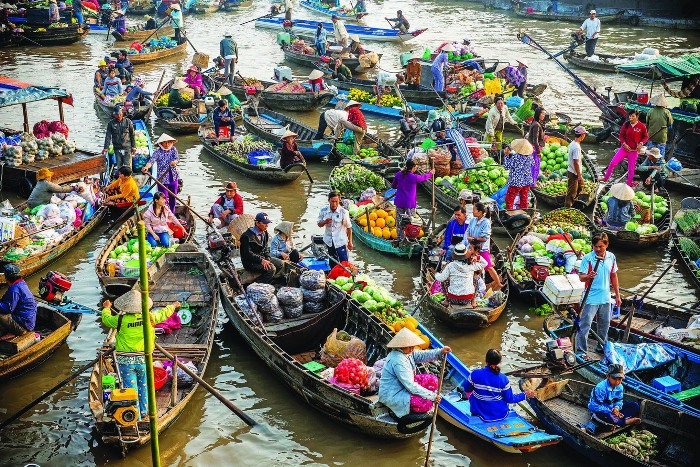 You cannot miss Cai Rang floating market in Can Tho Province, and the chance to buy things while rowing on a boat up and down the river - Photo: Internet
