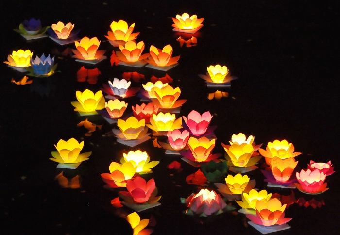 People buy candlelit paper flowers for the offerings on Hoai River in Hoi An (Vietnam) and wish for their own luck -  Photo: Internet
