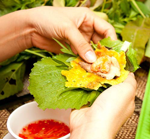 Wrap Banh Xeo in a large leaf of lettuce or mustard green, then dip in the sauce - Photo: Internet